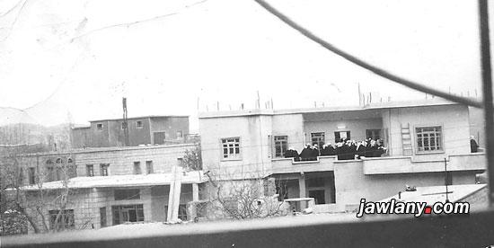 """التقطت الصورة في العام 1968 من بيت السيد محمد سعيد القضماني المشرف على ساحة سلطان الأطرش في مجدل شمس، ويعتقد أن المصور هو السيد محمد نفسه الذي عرف عنه اهتمامه بالتصوير والتوثيق. أما البيوت التي تظهر في الصورة فهي (من اليمين): حيث يتواجد عدد من رجال الدين على شرفة المنزل، هو بيت المرحوم الشيخ سلمان طاهر أبو صالح، ثم على يساره من الأمام بيت المرحوم الشيخ أبو رؤوف سليمان المرعي، خلفه يأتي بيت المرحوم سليم محمود، وقد قام مكانه اليوم بيت السيد عدنان محمود. أما المبنى الأخير في الخلف فهو مبنى """"ماتور الكهربا"""" القديم، وهو المبنى الأول الذي شكل محطة توليد الكهرباء في البلدة،"""